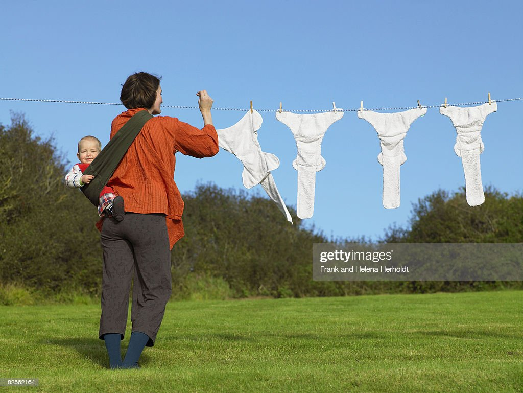 Mother and baby hanging nappies outside : Stock Photo