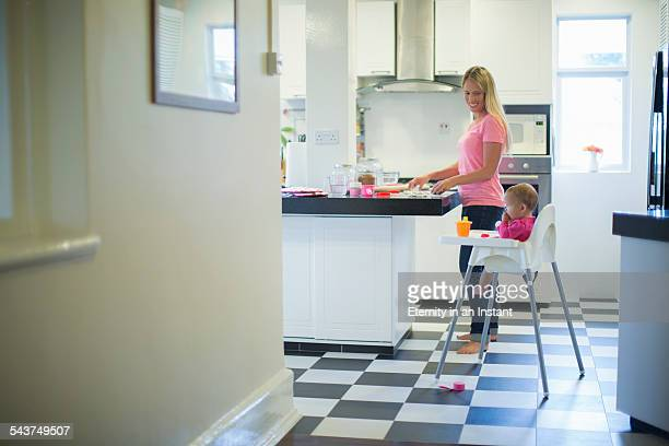 Mother and baby in kitchen making cookies