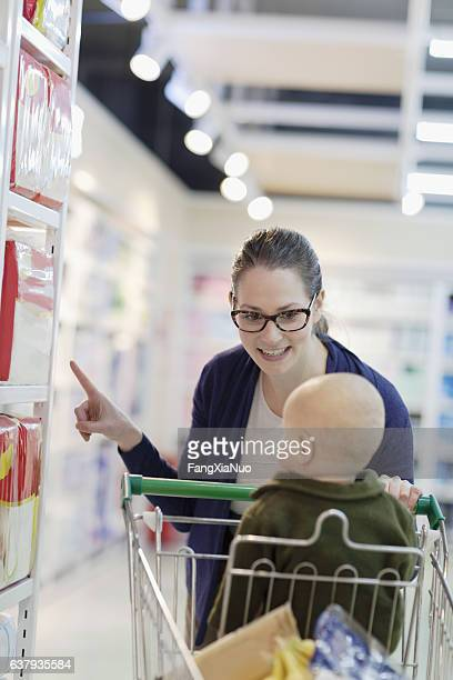 Mother and baby in store selecting diapers on shelf