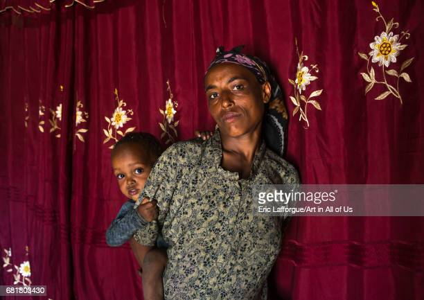 Mother and baby inside their house in front of a red curtain Kembata Alaba Kuito Ethiopia on March 8 2016 in Alaba Kuito Ethiopia