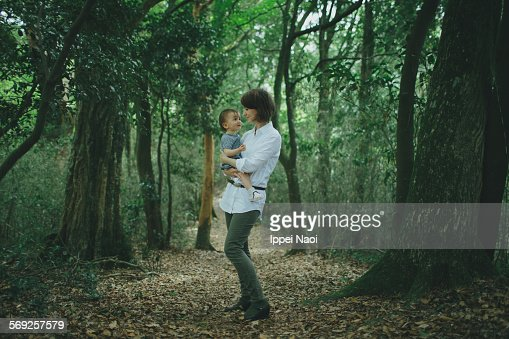 Mother and baby looking at each other in forest