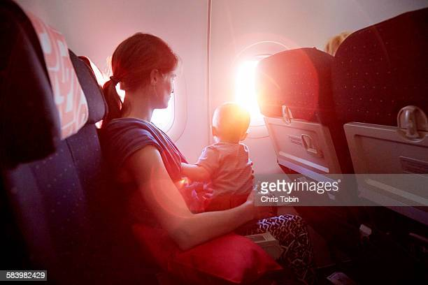 Mother and Baby on airplane looking out of window