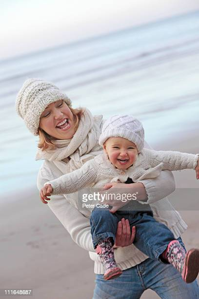 mother and baby playing on beach in winter