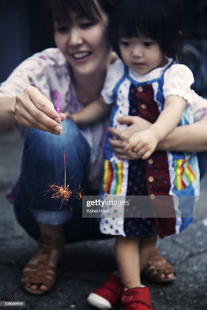 mother and baby playing small fireworks : Stock Photo