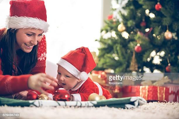 Madre y bebé jugando con adornos navideños
