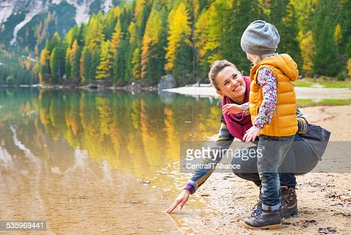 Mother and baby playing with water on lake braies, italy : Stock Photo
