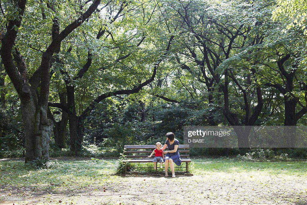 Mother and baby sit on bench in forest. : Foto de stock