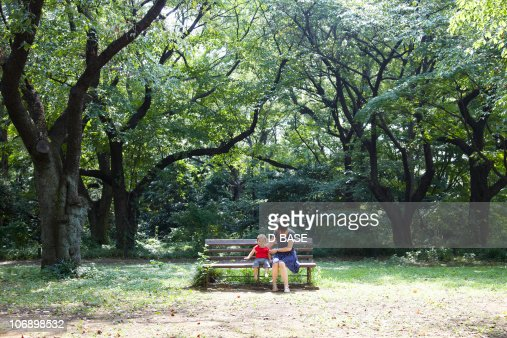 Mother and baby sit on bench in forest. : Stock-Foto