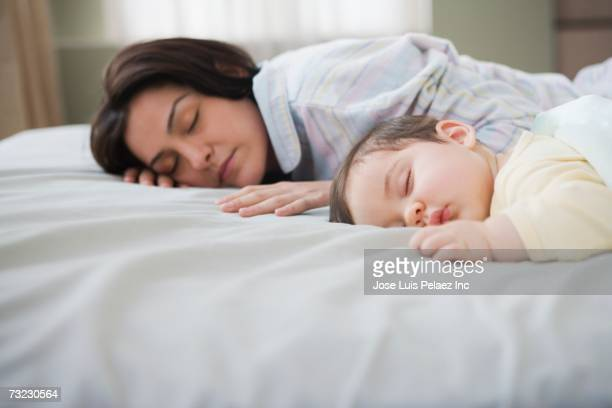 Mother and baby sleeping on bed