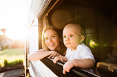 Beautiful young mother and her baby son in a camper van on a summer day