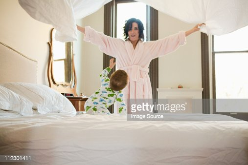 Mother and baby son making bed