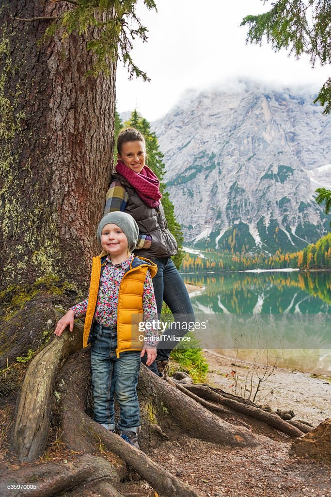 Mother and baby standing near tree on lake braies, italy : Stock Photo