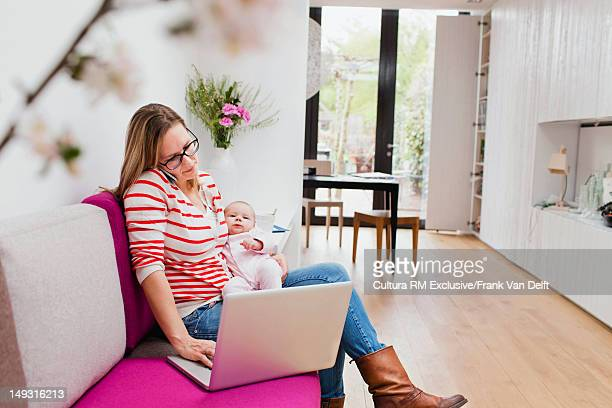 Mother and baby using laptop on sofa