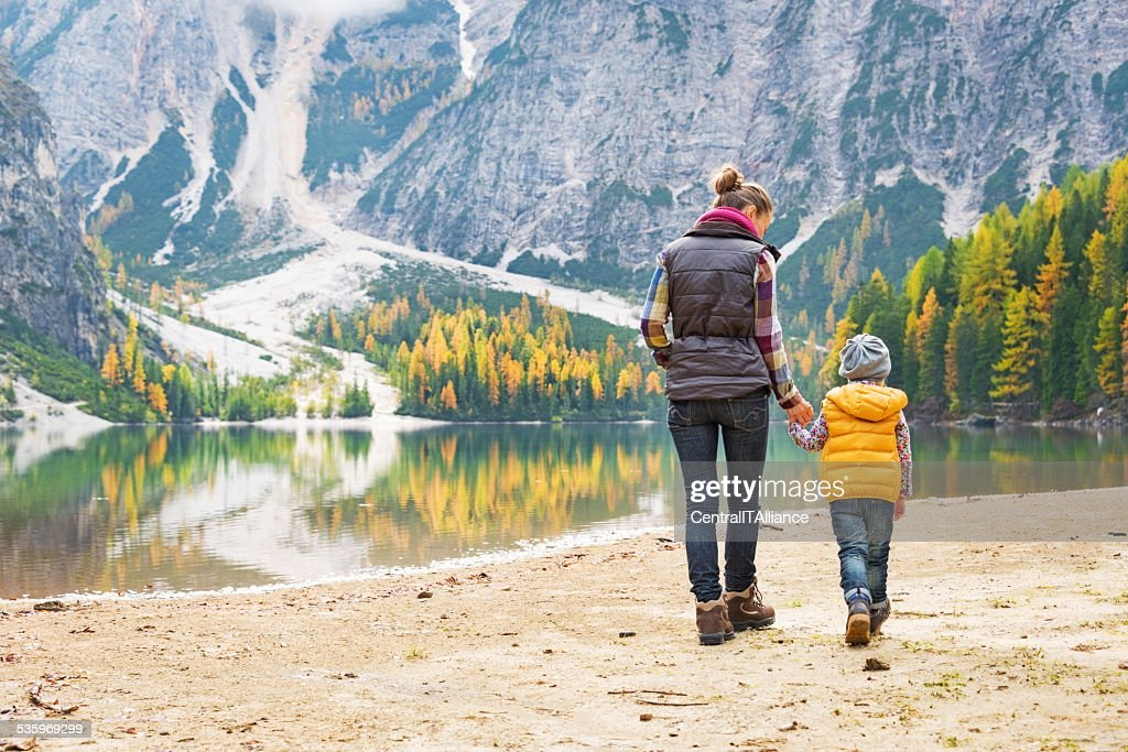 Mother and baby walking on lake braies, italy : Stock Photo