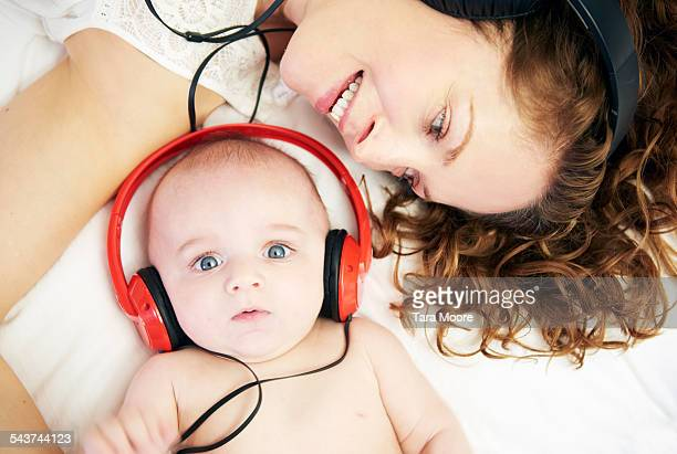 Mother and baby with headphones at home in bed