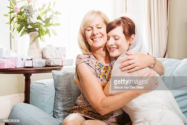 mother and bride embracing sitting on sofa.