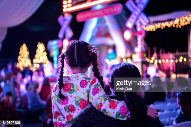 Mother and child are waiting for Santa at a Christmas tree lighting ceremony.