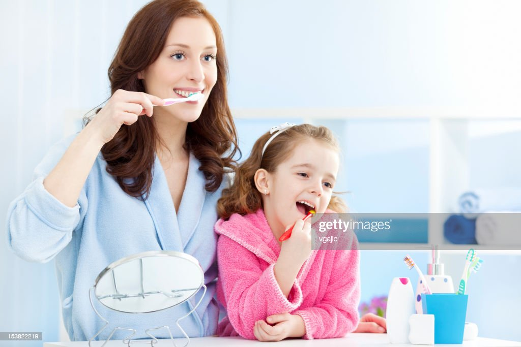 Mother and child brushing teeth together. : Stock Photo