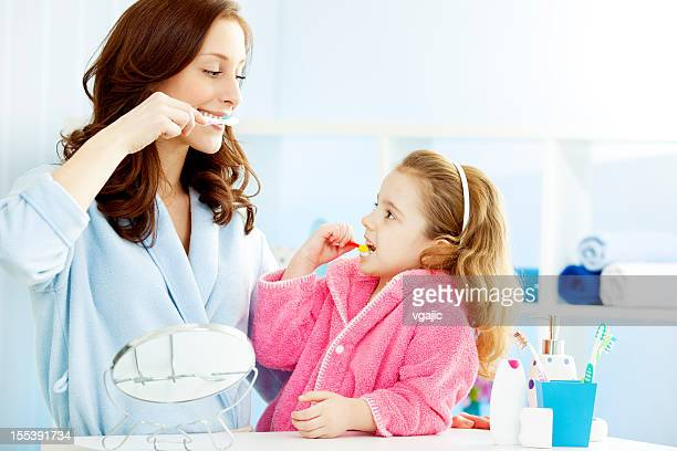 Mother and child brushing teeth together.
