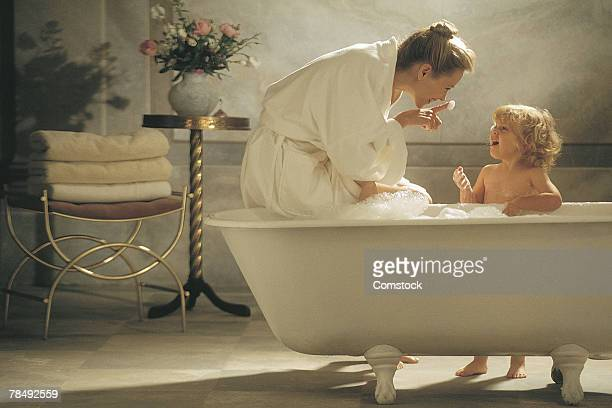 Mother and child by bathtub