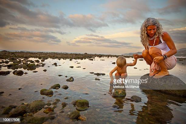 Mother and child explore beach at sunset