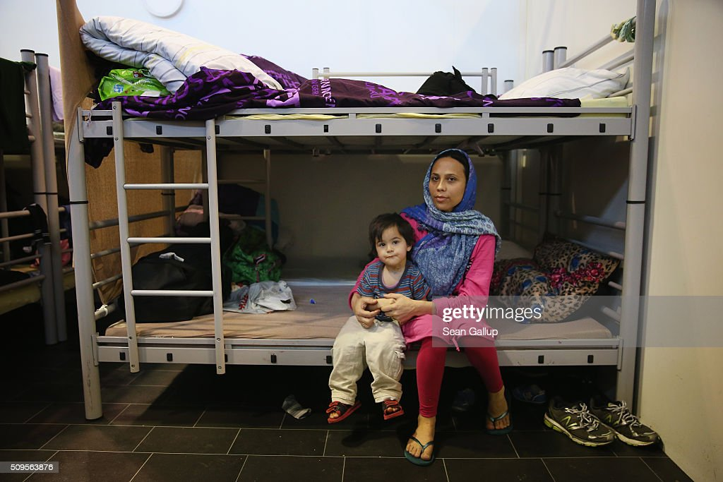 A mother and child from Afghanistan sit on a bunk bed in the cubicle they share with other family members in Hangar 7 at former Tempelhof Airport on February 11, 2016 in Berlin, Germany. Tempelhof, once an airport in the city center and first built in the 1930s, now houses approximately 2,600 refugees in three former hangars. Berlin city authorities recently approved plans to expand its capacity to house the newcomers with an additional 90 shelters with space for 30,000 people. An estimated 50,000-80,000 migrants and refugees already live in Berlin. Germany received 1.1 million refugees and migrants in 2015 and is expecting to continue to receive large numbers in 2016.