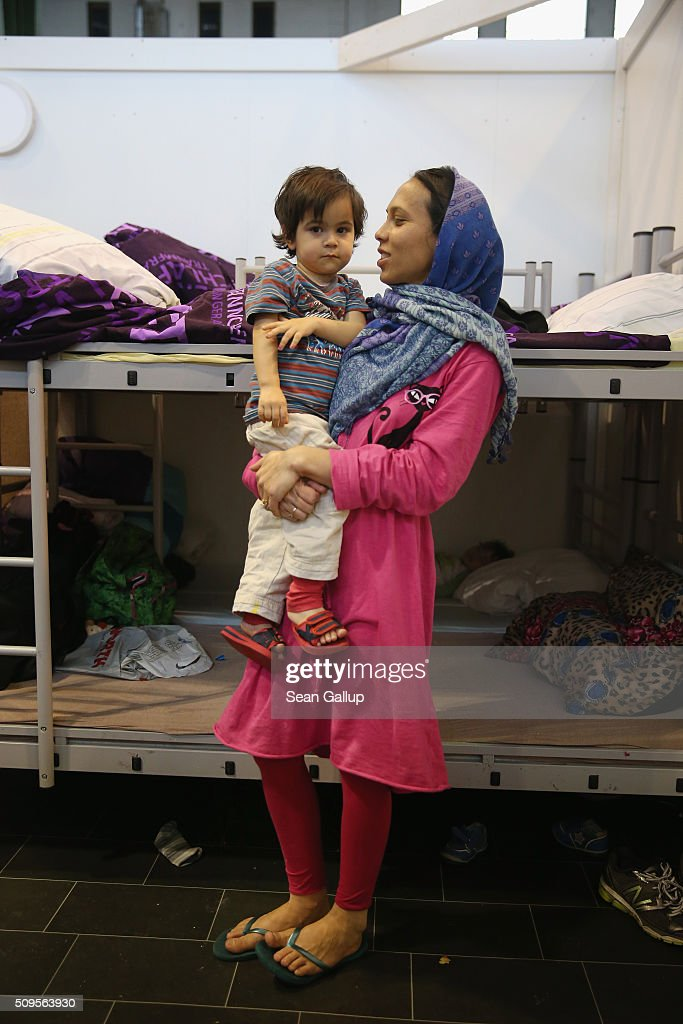 A mother and child from Afghanistan stand among bunk beds in the cubicle they share with other family members in Hangar 7 at former Tempelhof Airport on February 11, 2016 in Berlin, Germany. Tempelhof, once an airport in the city center and first built in the 1930s, now houses approximately 2,600 refugees in three former hangars. Berlin city authorities recently approved plans to expand its capacity to house the newcomers with an additional 90 shelters with space for 30,000 people. An estimated 50,000-80,000 migrants and refugees already live in Berlin. Germany received 1.1 million refugees and migrants in 2015 and is expecting to continue to receive large numbers in 2016.