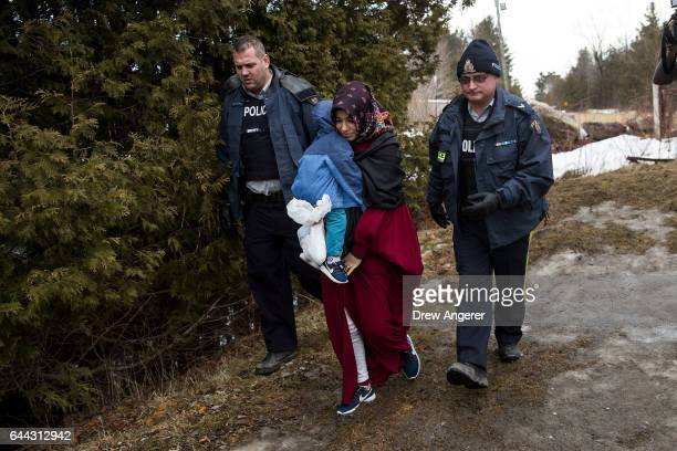 A mother and child from Turkey are escorted by Royal Canadian Mounted Police after they crossed the USCanada border into Canada February 23 2017 in...