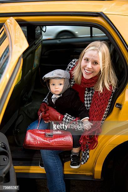 Mother and child getting out of a yellow cab