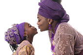 Mother and child girl kissing.African traditional purple clothing. Isolated on the white studio background