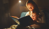 mother and child girl reading a book in bed before going to sleep