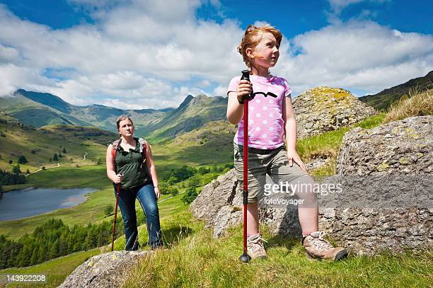Mother and child hiking in picturesque mountains