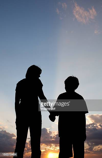 Mother and Child holding hands under the sunset