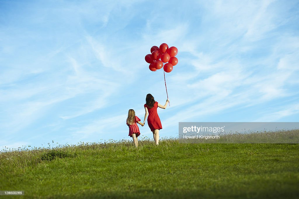 Mother and child holding red balloons : Stock Photo
