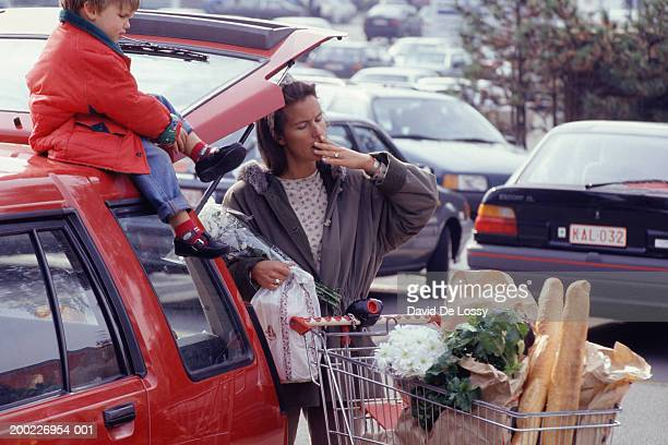 Mother and child (3-4 years) in supermarket car park with shopping, three quarter length