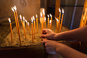 Mother and child lighting and holding a candle in Orthodox Church