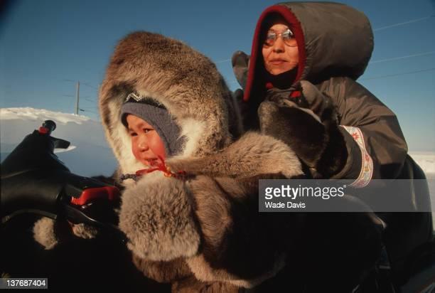 Mother and child on snow mobile Igloolik Nunavut Canada 2006