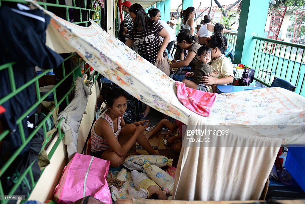 A mother and child, one of the thousands affected by flooding due to heavy rains exacerbated by Tropical Storm Trami, rest on their makeshift shelter inside a school building serving as an evacuation center in Marikina, east of Manila on August 21, 2013, as rains pounded the capital city for the third day. Heavy rain pounded the Philippine capital and surrounding areas for a third day August 21, adding to the misery of nearly 300,0000 exhausted people displaced from their flooded homes. AFP PHOTO / TED ALJIBE