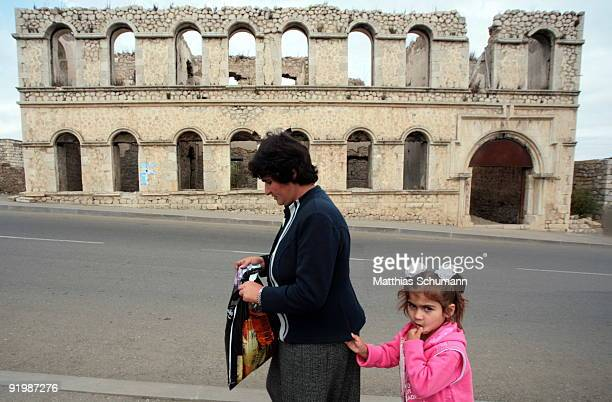 Mother and child pass a ruined building in Shushi on September 24 2007 in NagornoKarabakh Azerbaijan Shushi is a town in the disputed region of...