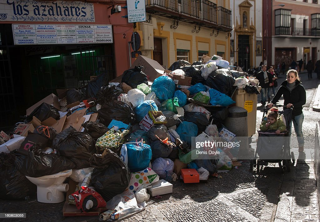 A mother and child pass uncollected garbage during the 10th day of the Seville waste disposal strike on February 6, 2013 in Seville, Spain. Workers are striking over demands they take a 5% pay cut and extent their working week to 37.5 hours.