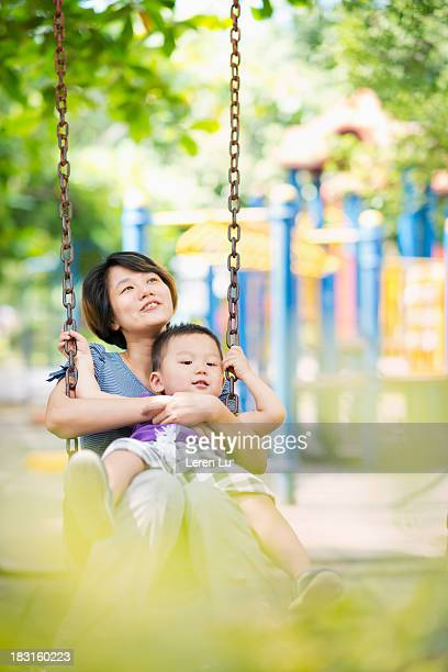 Mother and child play swing happily