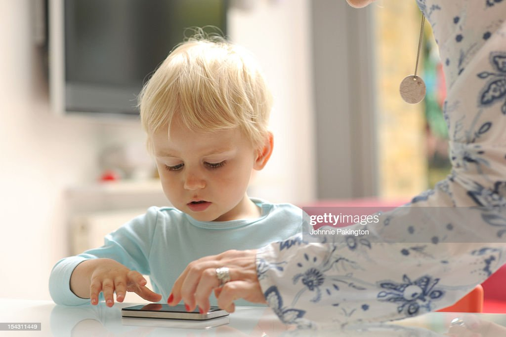 Mother and child playing with a smartphone : Stock Photo