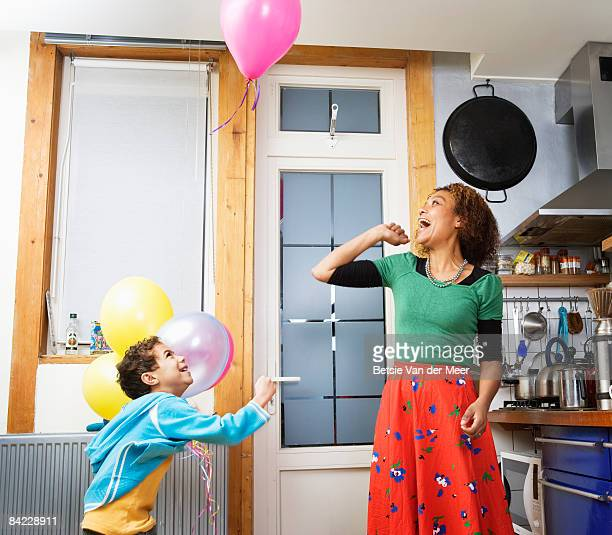 mother and child playing with balloons.