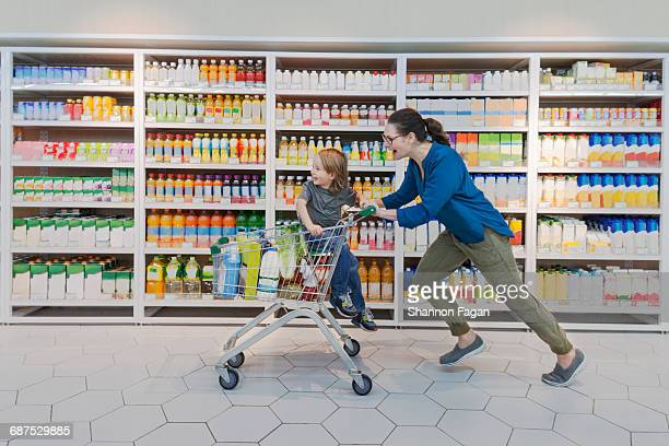 Mother and child racing through supermarket aisle