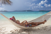mother and child relaxing in hammock at a tropical beach
