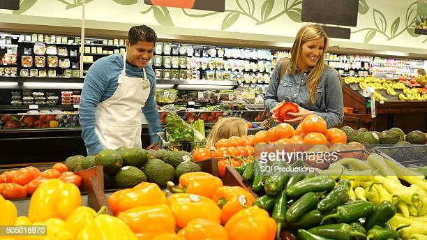 Mother and child shopping for produce in grocery store supermarket