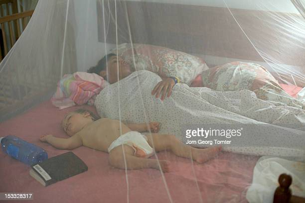 Mother and child sleeping behind mosquito net