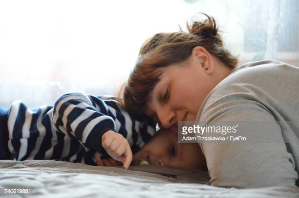 Mother And Child Sleeping On Bed At Home