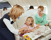 Mother and child smiling at female air stewardess on plane