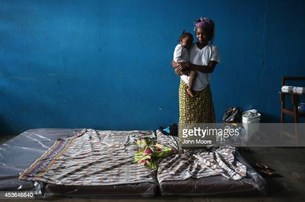 A mother and child stand atop their mattresses in a classroom now used as Ebola isolation ward on August 15 2014 in Monrovia Liberia People suspected...